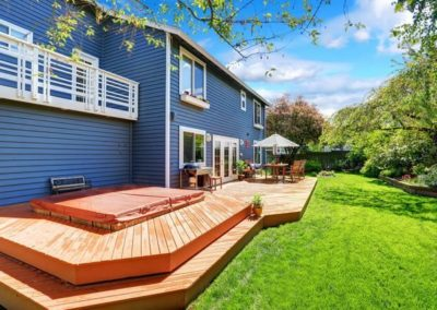 decking-material-options-best-outdoor-decking-material-blue-house-with-spacious-wooden-decking-wood-dining-set-with-umbrella-spacious-gar